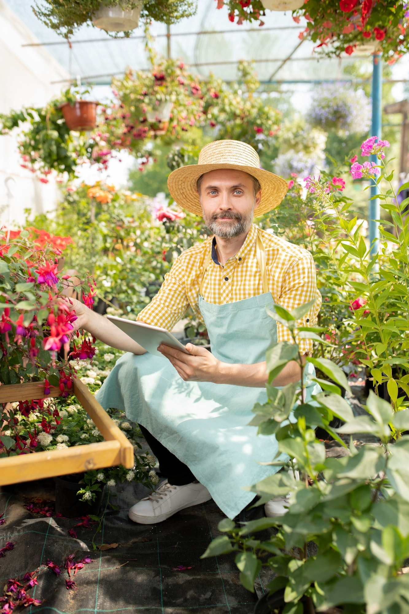 Contemporary farmer in workwear searching for names of new sorts of flowers